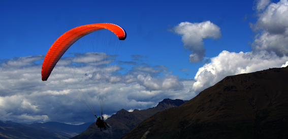 orange paraglider flying towards clouds