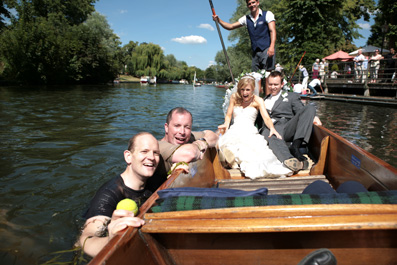 bride in punt on river cam with swimmers